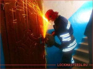 Сотрудник МЧС вскрывает входную дверь при помощи болгарки